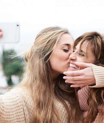 Young woman kissing and hugging her smiling mother while making selfie